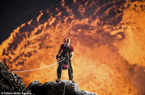 Daredevil adventure-seeker abseils into active volcano with molten lava before doing a handstand on the edge